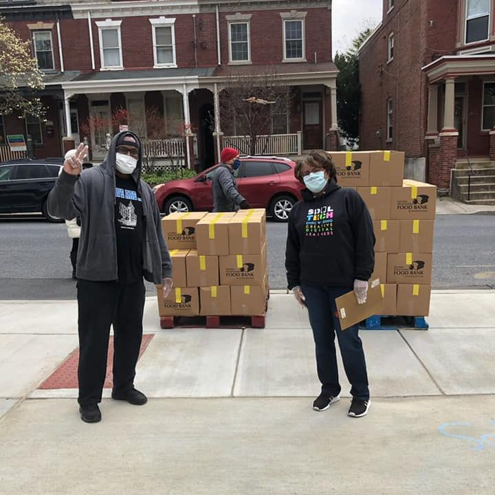 Two people wearing masks and delivering meals
