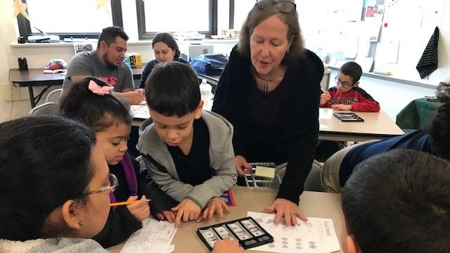 Teacher working with parents and their children in a classroom