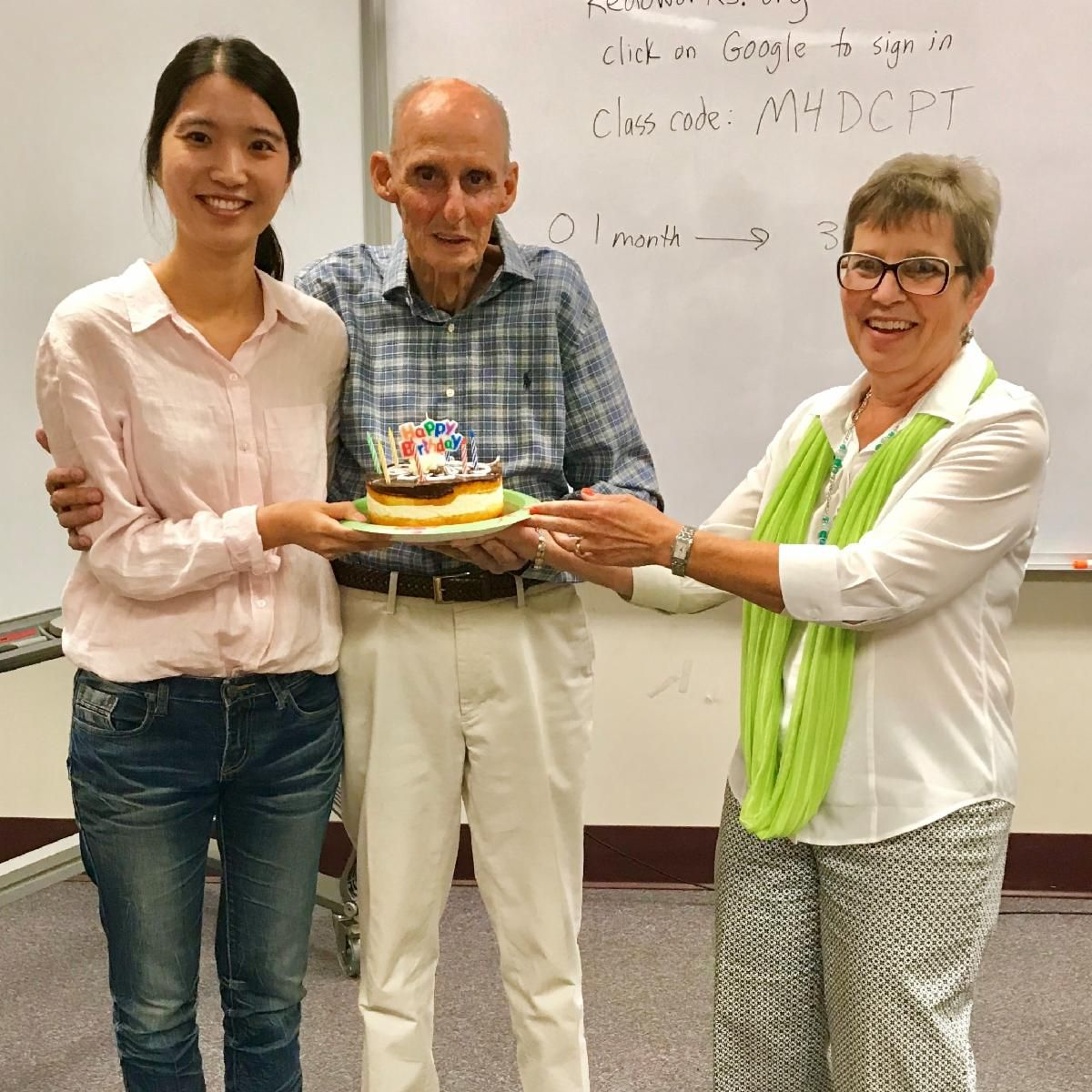 Three people smiling and holding a cake