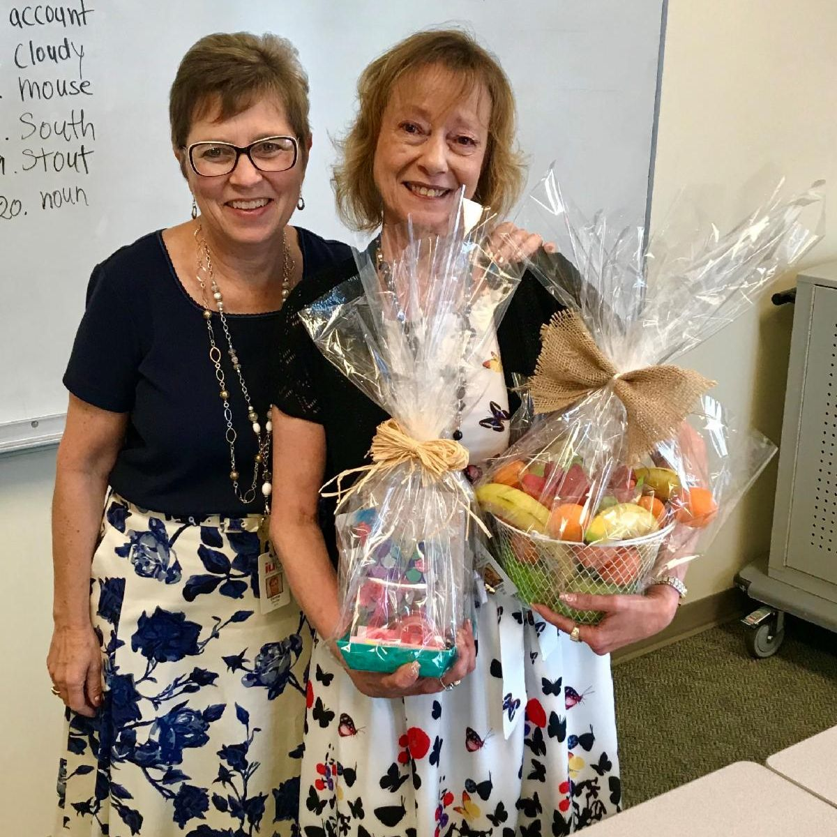 Two women smiling and holding gift baskets