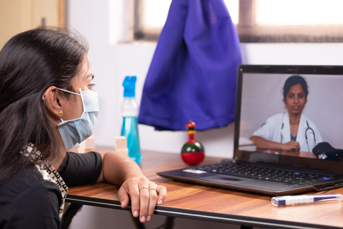 Concept of Online Chat_ telehealth_ or tele counseling with Nurse or Doctor on Screen during coronavirus or covid-19 pandemic - Girl in medical mask listining to doctor on laptop at home.