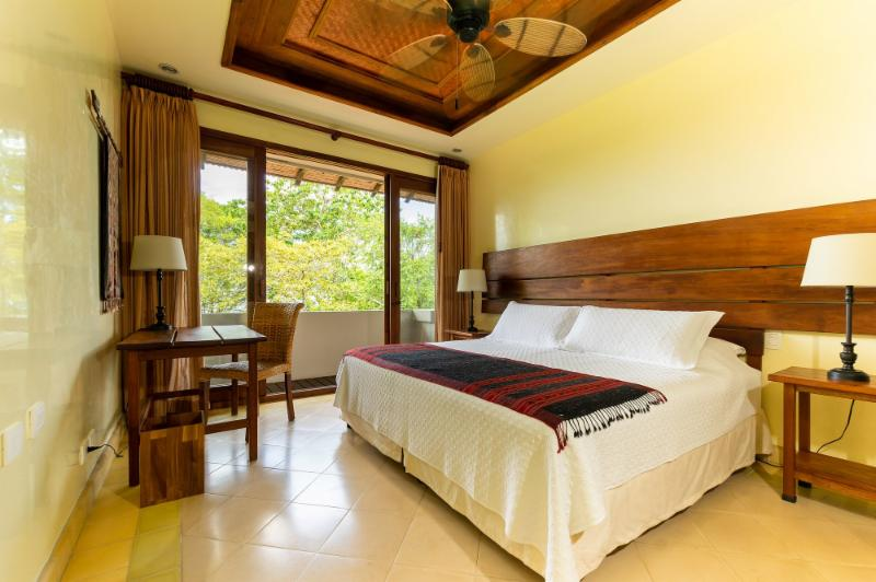 room with king size bed, desk and balcony