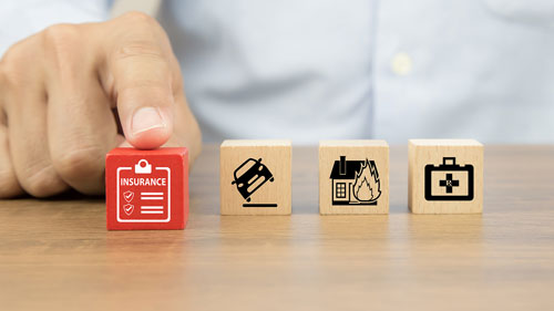 Hand pointing to wooden blocks indicating different types of insurance