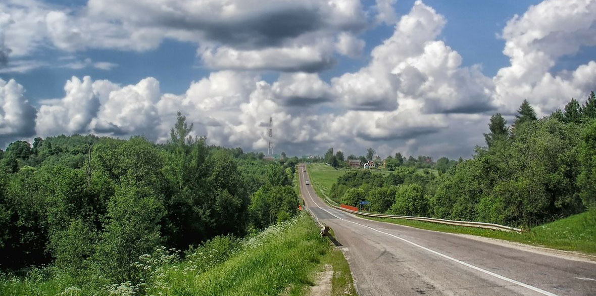 Highway through rolling hills with cloudy blue skies.