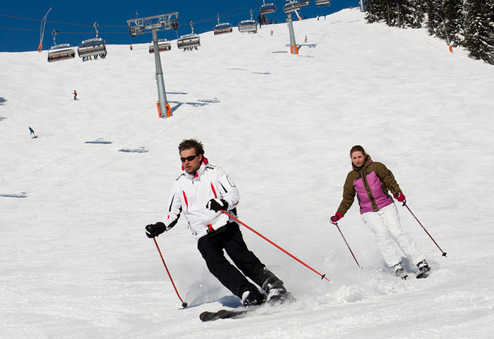 Man and woman downhill skiing with ski lift in the background.