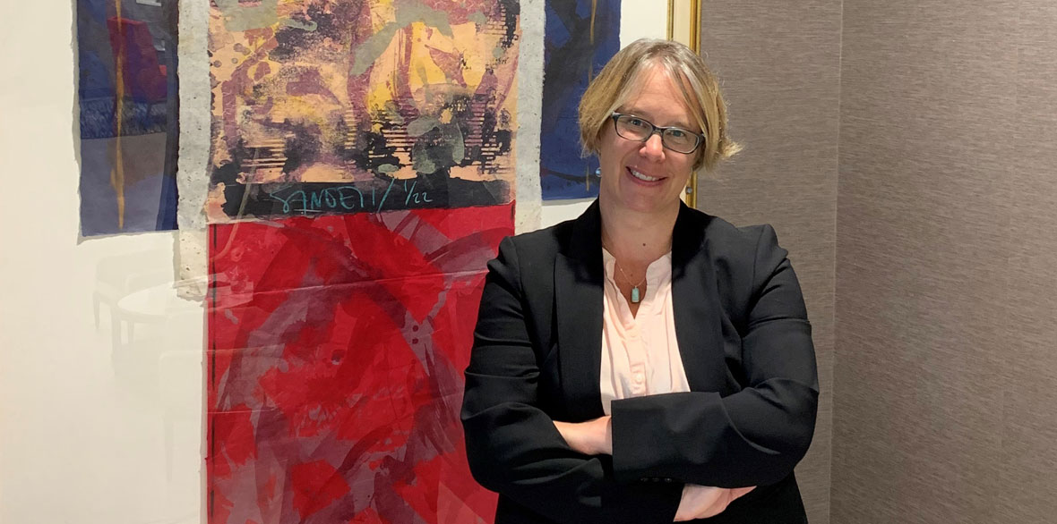 Sara Wilson Lommen Abdo Law Firm Smiling woman in a business suit standing with arms crossed in front of artwork.