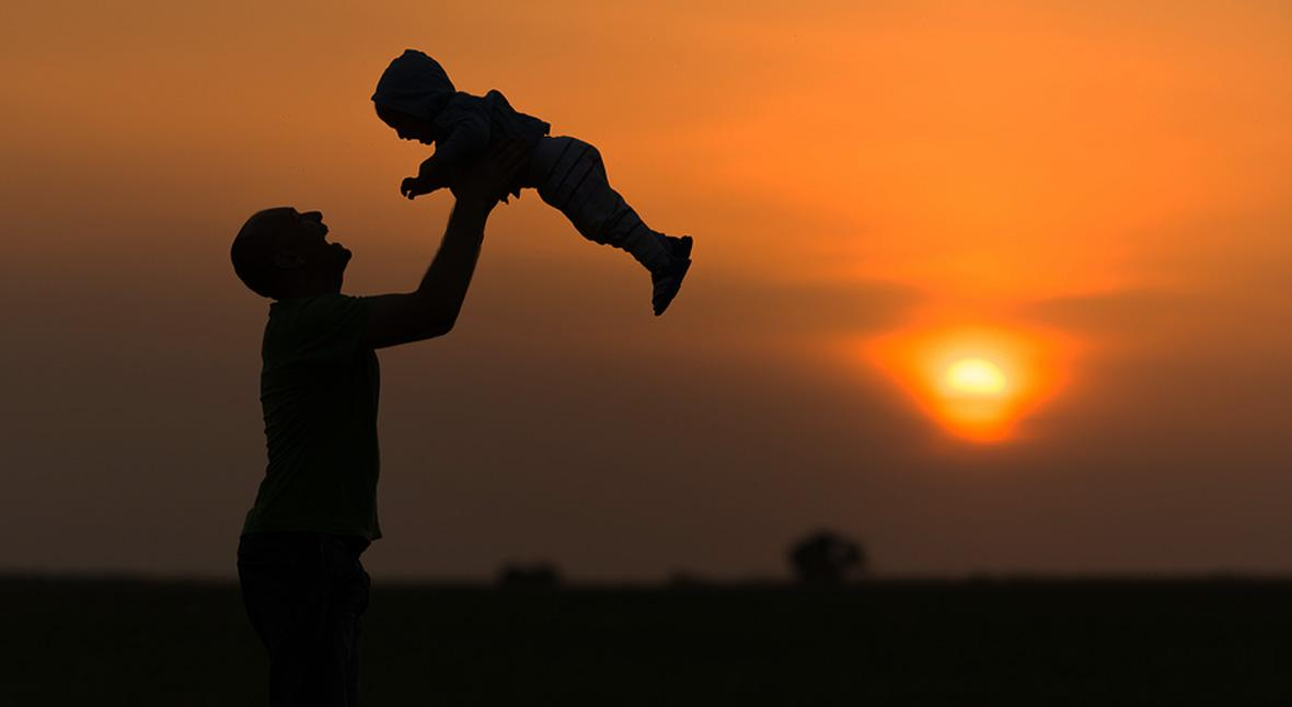 Silhouetted dad throwing baby at sunset.