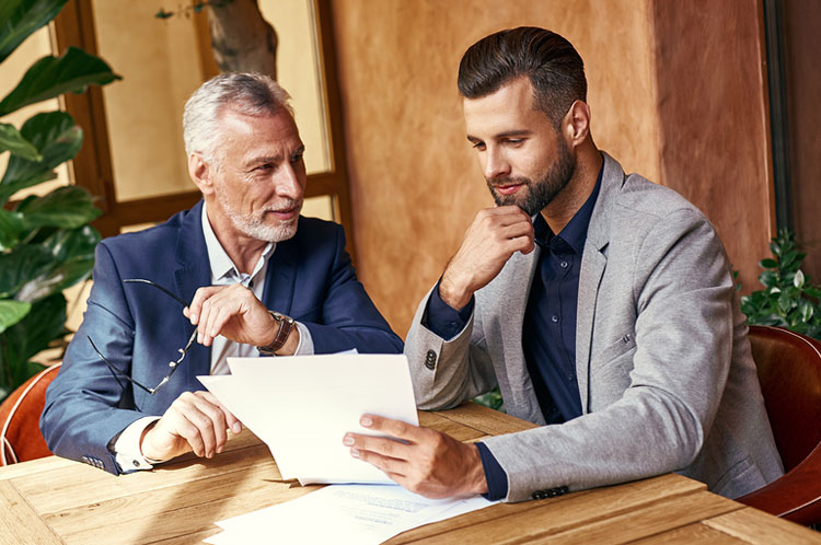 Father and son sitting at table looking at paperwork.