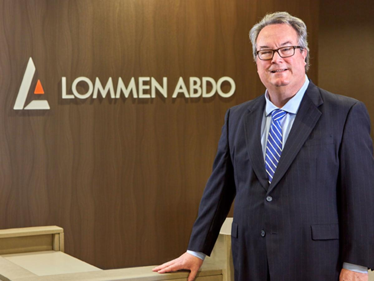 Smiling man in a business suit standing with his hand on a desk in front of Lommen Abdo logo