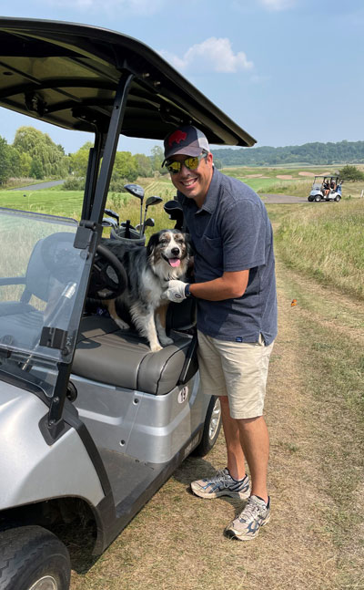 Attorney Cameron Kelly at the 2021 Hudson Daybreak Rotary Golf Tournament with the Troy Burne Coyote Patrol dog