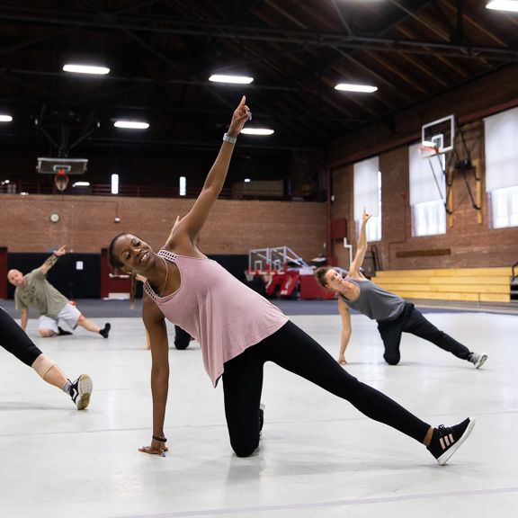 Shakia, a black woman, smiles while teaching a dance class in a large open gymnasium