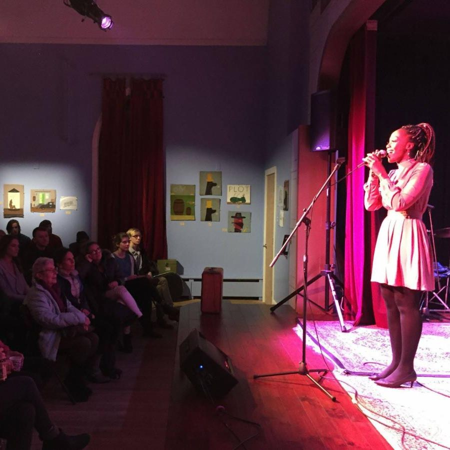 A woman speaks into a microphone on stage in front of a crowd in an intimate theater.