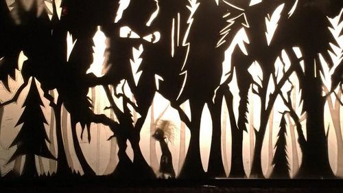 shadow puppet show depicting a girl-like figure with bewildered hair walking through a dark and creepy forest