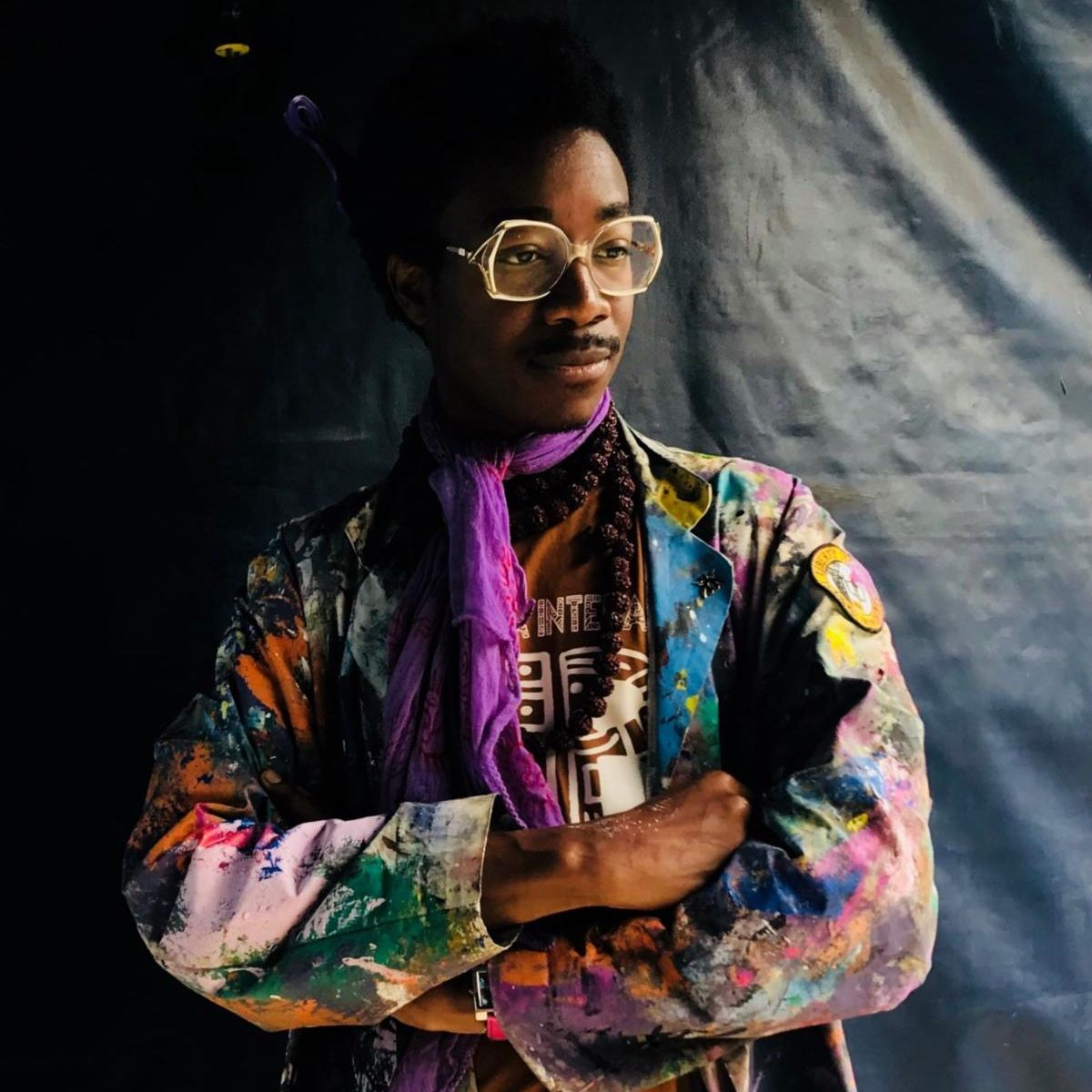 Kwadwo stands in front of a tarp background with his arms crossed. He is wearing a colorfully paint-smattered jacket.