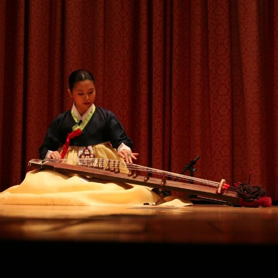 a musican sits on stage in traditional Korean attire. She plays the Gayageum - a stringed instrument that resembles the arm of a violin with many tall frets and strings.