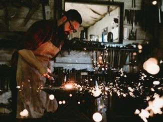 A blacksmith lets sparks fly as he labors on a project at the Greasy Luck Forge