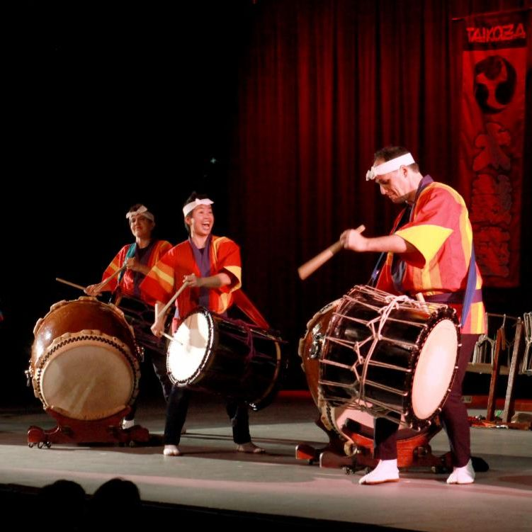 Several drummers energetically perform on stage, each in traditional Japanese dress with drums as big or bigger than each drummer.