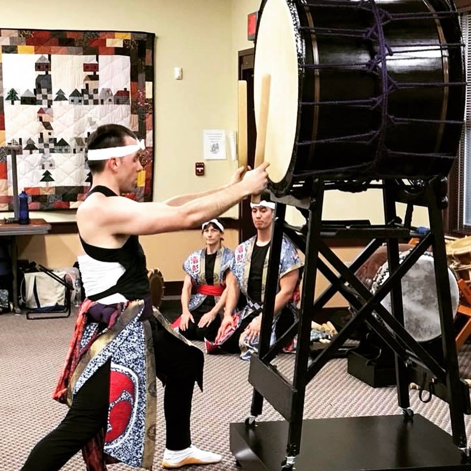 A person in traditional garments dramatically plays a large Taiko drum while similarly dressed onlookers kneel and listen.