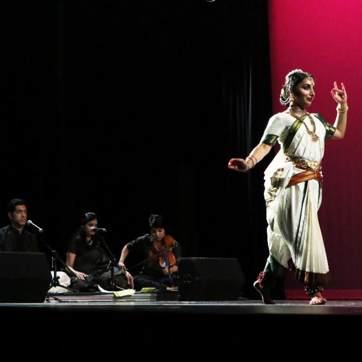 Madhvi Venkatesh performs a classical Indian dance style onstage. Sitting musicians play live music to accompany her dancing.