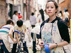 Michelle Nugent looks at the camera wearing an apron covered in paint. Behind her, a crowd of artists fill an alley way as they paint.