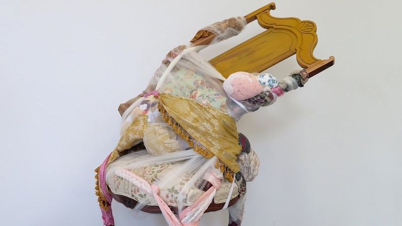 an antique chair twisted sideways with ornate fabric and fibers in whimsical patterns tied around the chair holding it together.