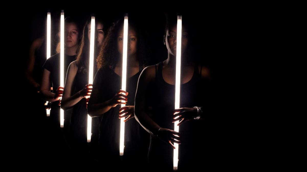 five dancers dressed in black, lined up in single file, each holding a long flourescent white light tube, extend into the darkness