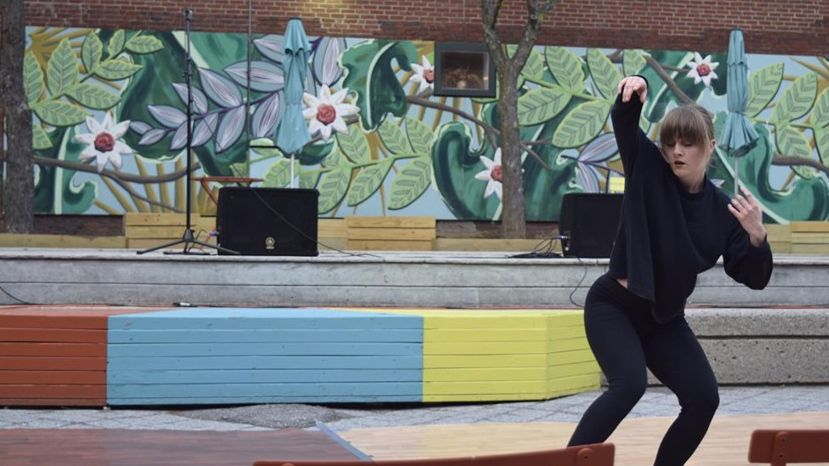A woman in black dances outdoors in front a of a brick wall painted with a colorful plant mural