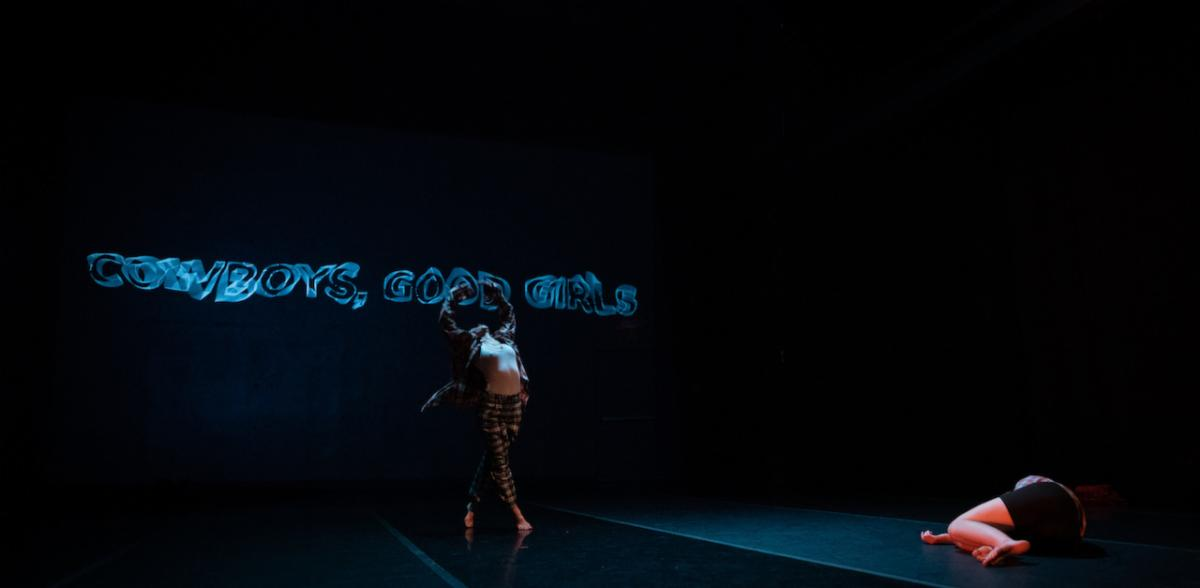 """On a dark stage, one dancer stretches dramatically upward while another lies crumpled on the floor. The words """"cowboys, good girls"""" are projected as blue neon"""