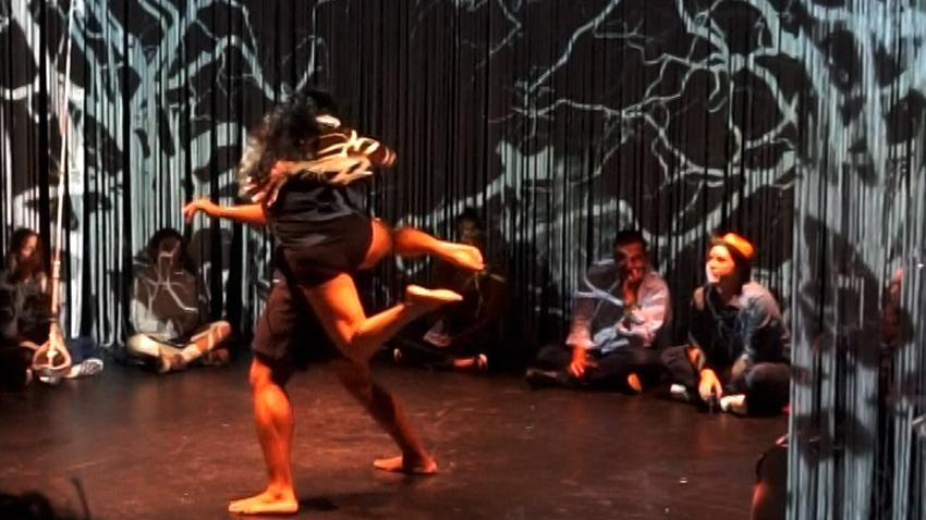 a dancer lifts a tinier dancer into the air during an in-the-round performance. audience members sit on the floor and projections of creepy leafless trees span the walls.