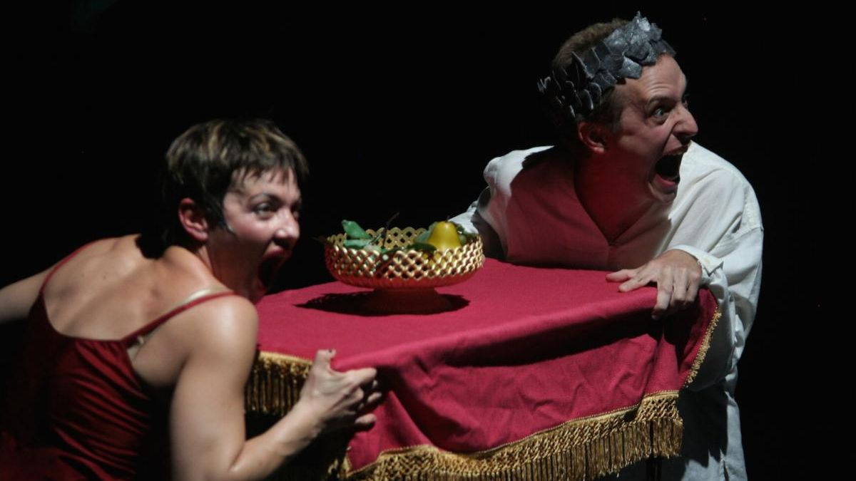 two performers hold onto either side of a table with a bowl of fruit on it. The performers are looking at the audience with hyperbolic happiness on their faces.