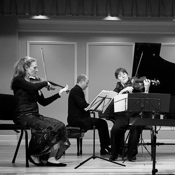 Musicians plan piano, violin, and viola onstage in an acoustic performance space.