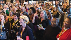 large crowd at a conference wearing yellow lanyards and cheering