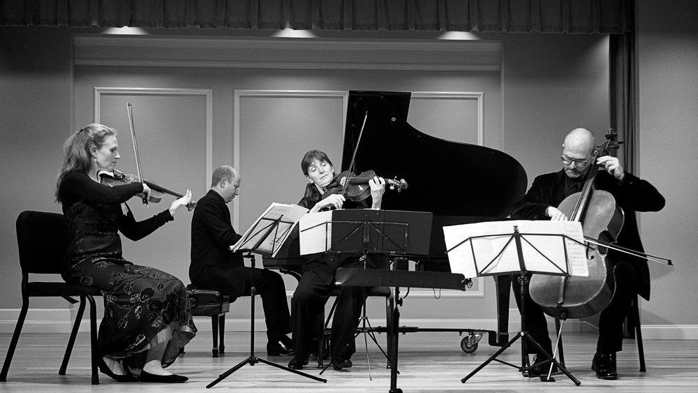 Two violinists, a cellist, and a pianist perform in an acoustic studio space