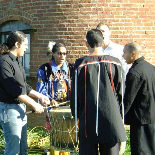 Five or so Black Brook Singers are gathered in song around a central drum playing Native American music of the Aquinnah nation.
