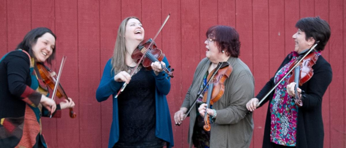 Four female fiddlers laugh animatedly in front of a red barn wall.