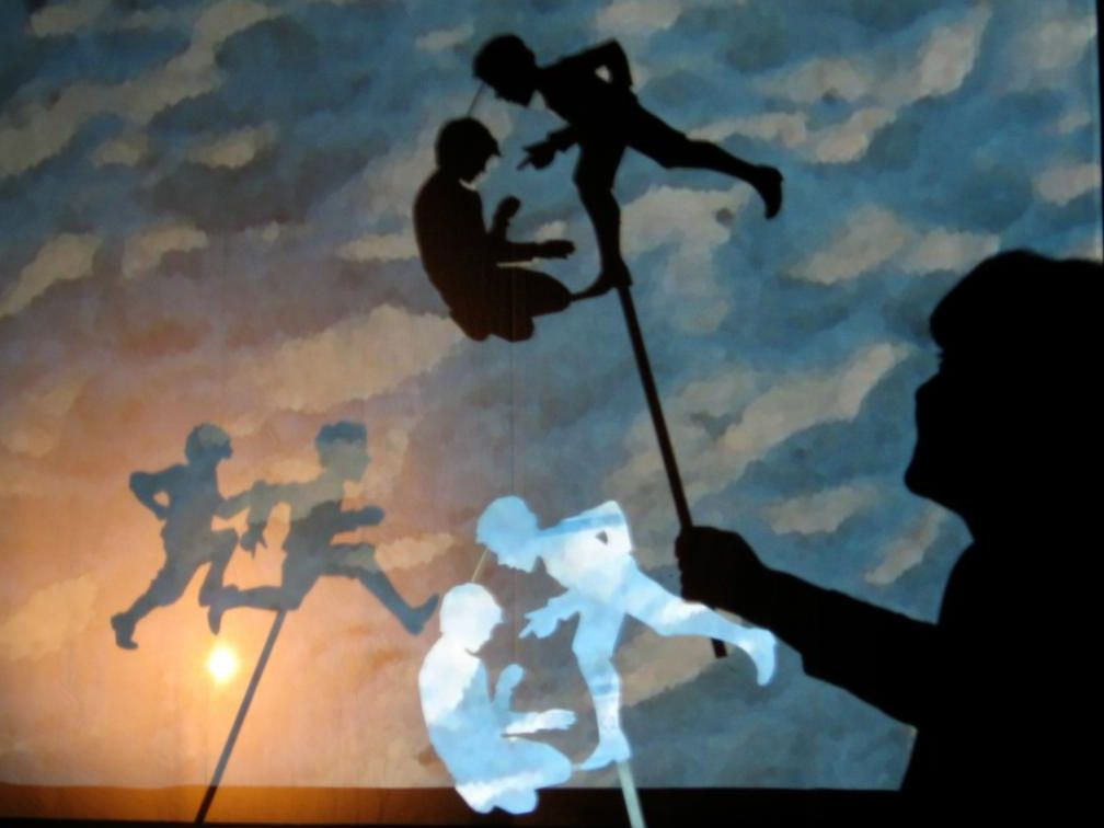 shadow puppets over lap in front of a daylight sky background. The boys chase each other, and boss each other around.