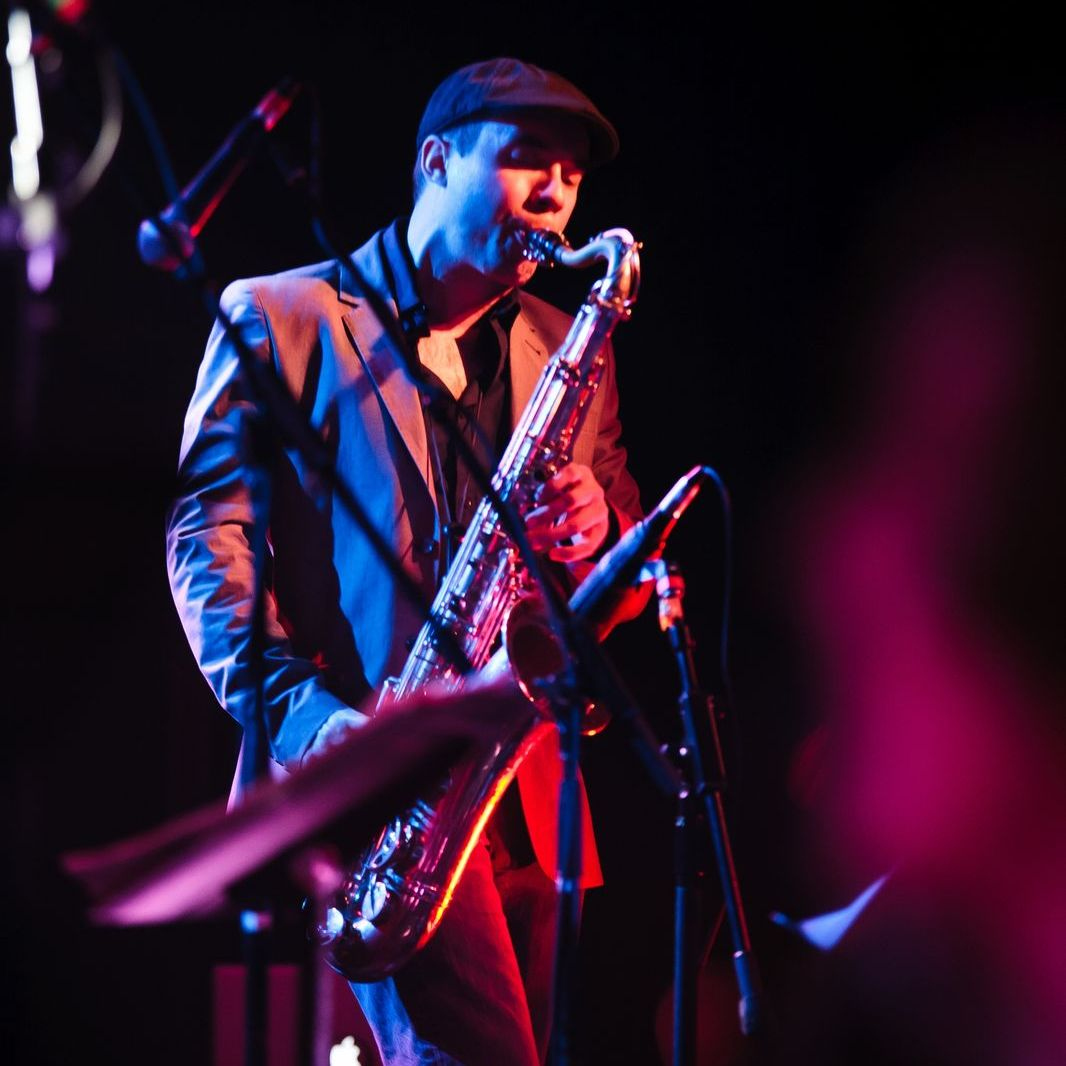 A musician plays a tenor saxophone onstage under dramatic purple lighting. He is wearing a newsboy cap.