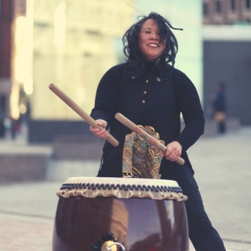 Karen wears a modern Japanese outfit while she joyfully plays a large drum outdoors.