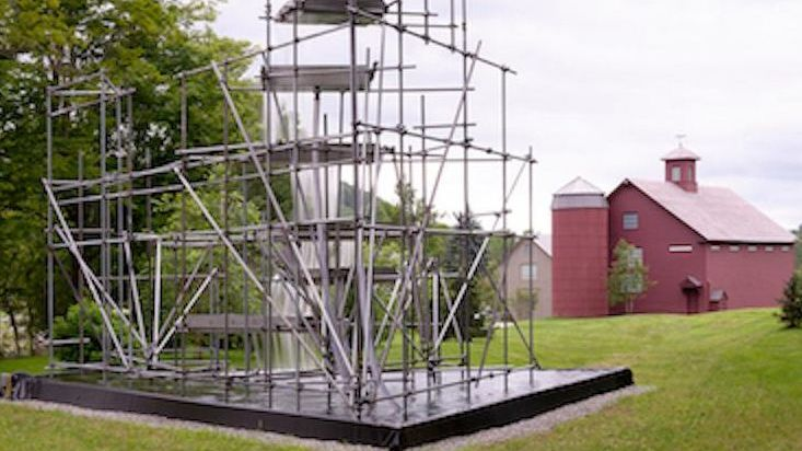scaffolding that looks like an aesthetic sculpture sits on a concrete slab outside of a red barn museum
