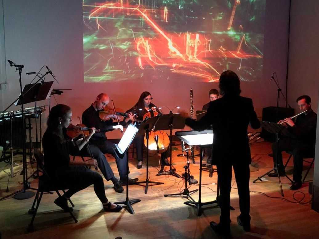 A conductor leads a group of classical musicians in song-performing in front of a dynamic projection of long exposure city lights