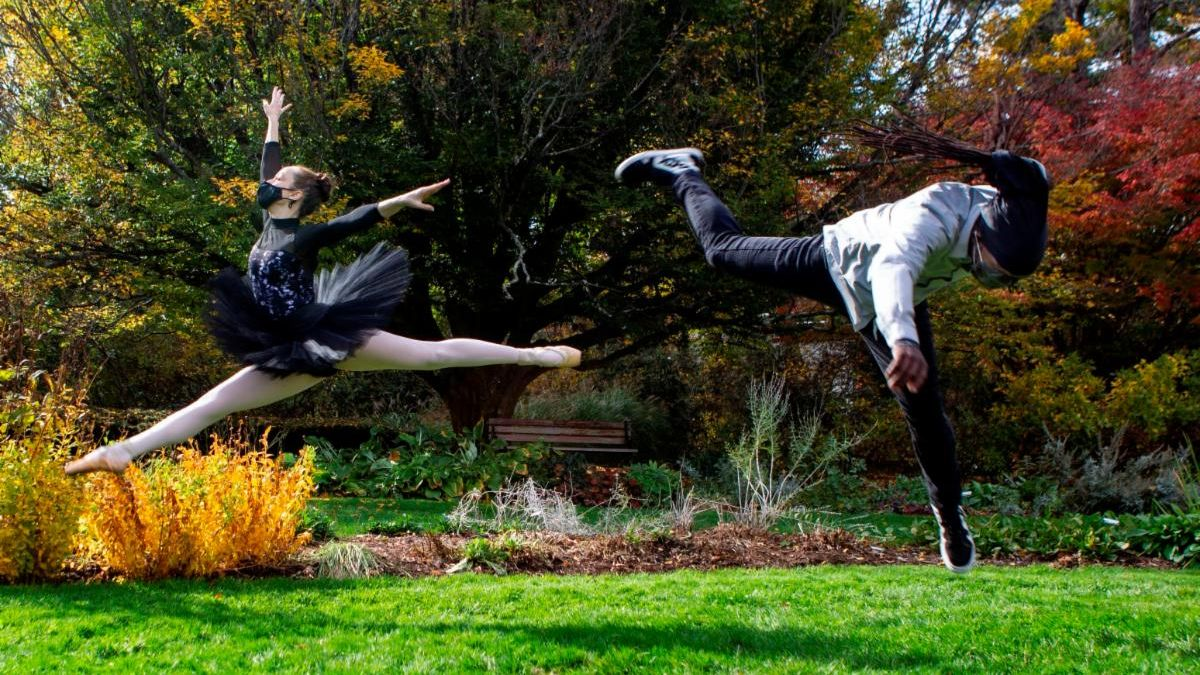 A ballerina in a tutu leaps in an autumnal garden, and another dancer athletically springs in the opposite direction.