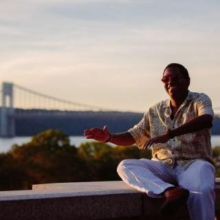 Yosvany, a cisgender black man, smiles in front of a bridge surrounded by trees. It is sunset and Yosvany joyfully taps out a musical rhythm with his arms