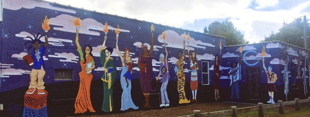 a painted mural on a cinderblock wall; women dressed in various cultural heritage outfits hold torches high.