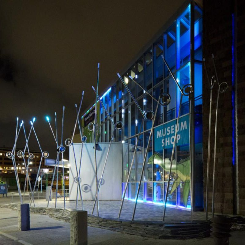 """A nighttime view of a kinetic metal structure by Evie Lovett is assembled of many long sticks and poles in front of a sign that reads """"museum shop"""""""