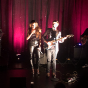 Tyler, a cis white man, plays guitar on a small stage next to a woman at a microphone. The stage curtains are deep red