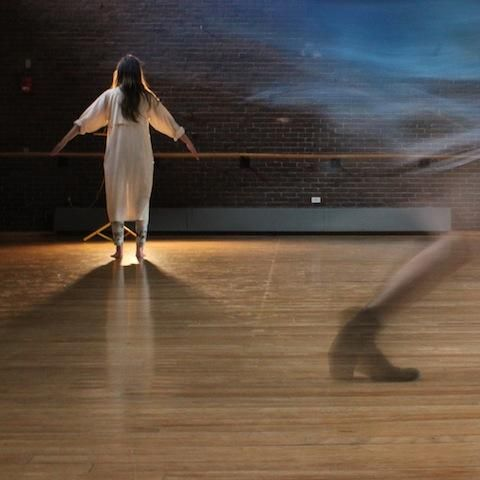 A woman in a night gown stands dramatically in front of a lamp in a performance studio. The ghost of another dancer mid-twirl is downstage from her.
