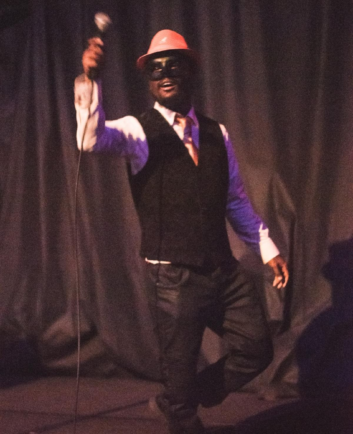 An onstage performer dressed in a suit, wearing a hat, and a black mask for the eyes holds a microphone high in the air.