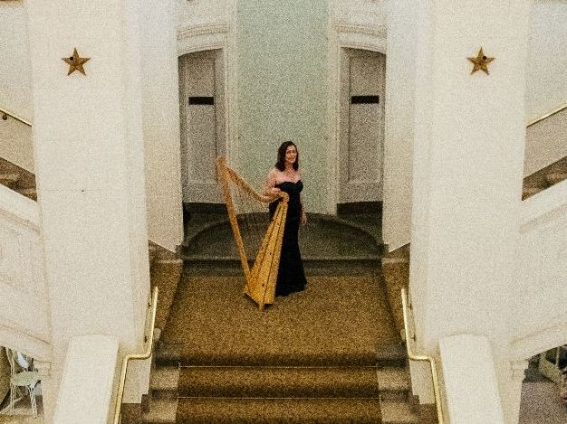 Zoe poses with her harp on the landing of stairs in the lobby of a giant concert hall.
