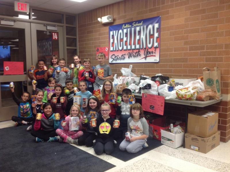 Students at Fulton pose with food they collected during a food drive.