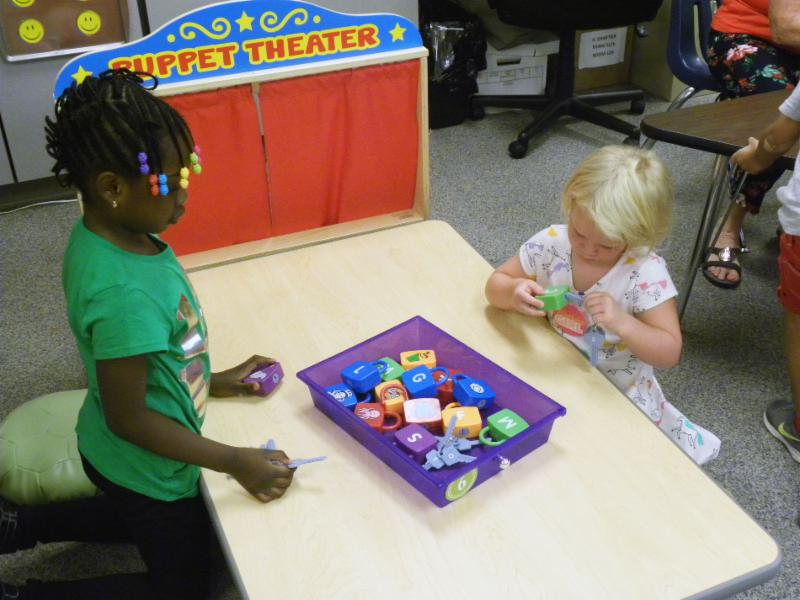 Kindergarten students use toys to learn numbers.